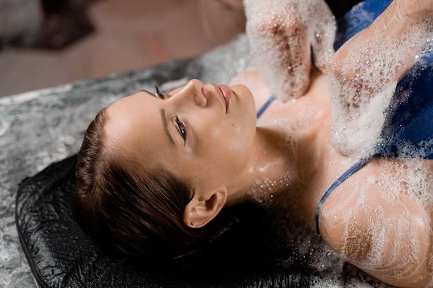Massaggio peeling con schiuma ravvicinata per il modello nella spa. relax nell'hammam turco.