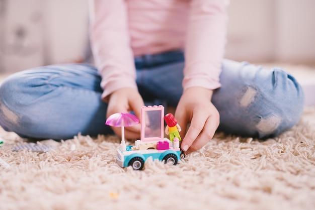 Chiuda sulla vista del fuoco di un'automobile del giocattolo di plastica con l'ombrello e la finestra rosa sul tappeto mentre la bambina gioca con loro.