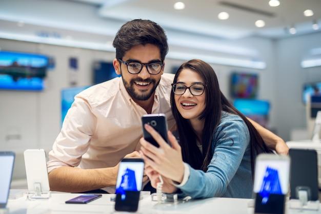 Primo piano vista di messa a fuoco di un affascinante giovane studente che abbraccia alla moda amore coppia prendendo un selfie con il nuovo cellulare in un negozio di tecnologia.