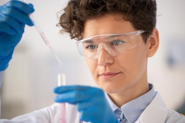 Primo piano del chimico concentrato in occhiali protettivi che cadono reagente durante l'esame della reazione chimica