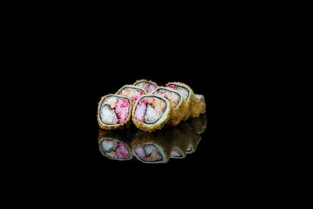 Un primo piano di rotoli di sushi fritto cibo isolato sulla riflessione nera