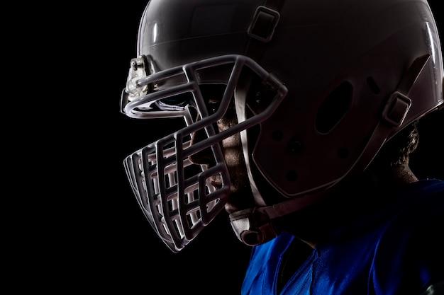 Primo piano di un giocatore di football con una divisa blu su un muro nero