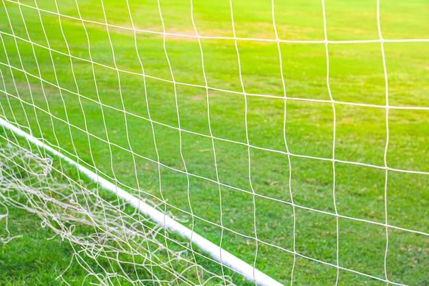 Chiuda in su della rete della porta di calcio di calcio con erba verde
