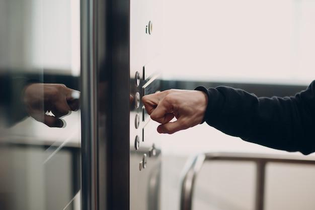 Primo piano dell'osso dell'indice che preme l'ascensore del pulsante durante la pandemia di coronavirus covid-19 concetto di quarantena