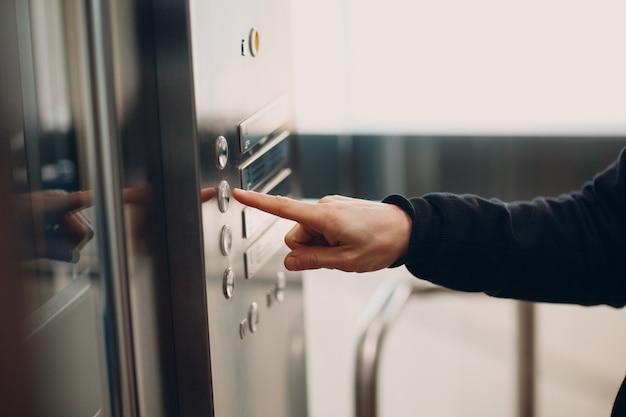 Primo piano dell'indice che preme l'ascensore del pulsante durante il concetto di quarantena covid di pandemia di coronavirus