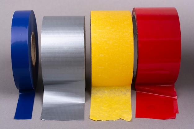 Primo piano di quattro rotoli di nastro adesivo multicolore.
