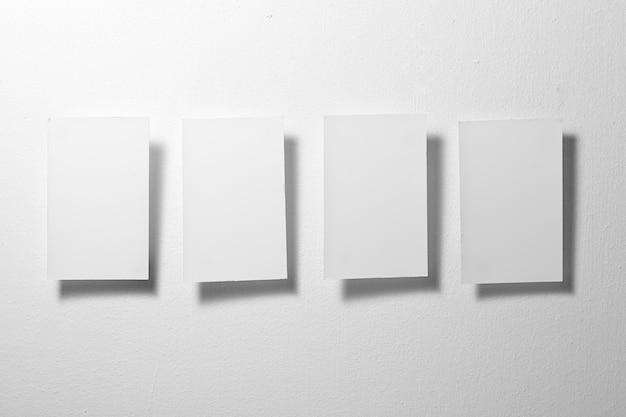 Chiudere quattro fogli di carta bianca su sfondo grigio
