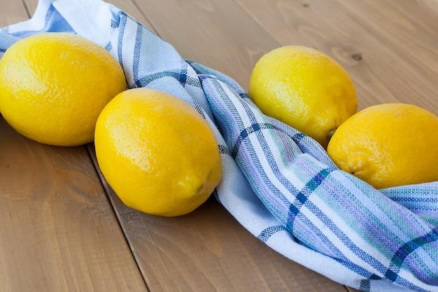 Primo piano di quattro limoni gialli su una vecchia superficie di legno con un asciugamano