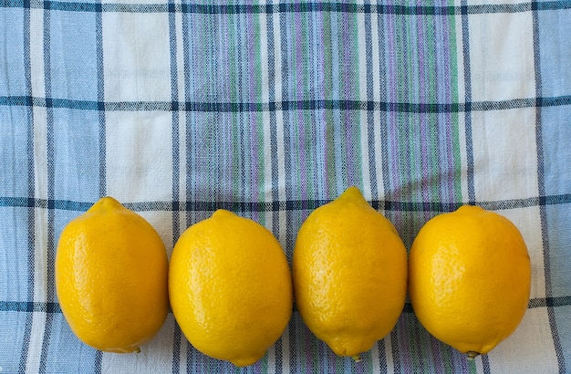 Primo piano di quattro limoni gialli su un asciugamano