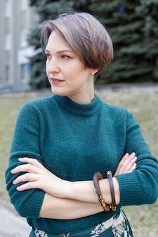 Frammento di primo piano di un maglione di lana femminile. ragazza in un vestito lavorato a maglia verde. maglione lavorato a maglia verde. ragazza vestita alla moda. vestiti caldi invernali da donna.