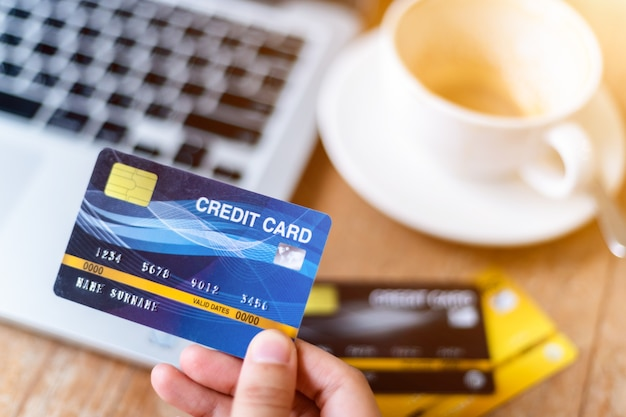 Close-up di persone freelance business femminile mano che tiene le carte di credito casual utilizzando il computer portatile
