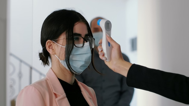 Primo piano del libero professionista misurare la temperatura dei colleghi utilizzando un termometro medico per proteggere l'assistenza sanitaria. squadra che rispetta la distanza sociale per evitare l'infezione da virus