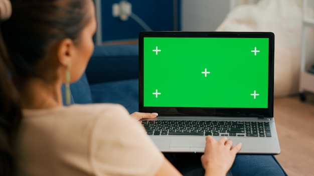 Primo piano del libero professionista che utilizza il computer portatile con display chroma key schermo verde finto mentre è seduto sul divano nel soggiorno., donna che lavora per affari personali utilizzando pc isolato