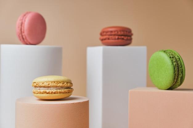 Close up french macarons colorati su piedistalli geometrici alla moda su una superficie beige
