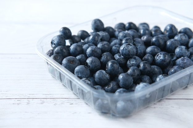 Primo piano di bacche blu fresche in un contenitore di plastica sul tavolo