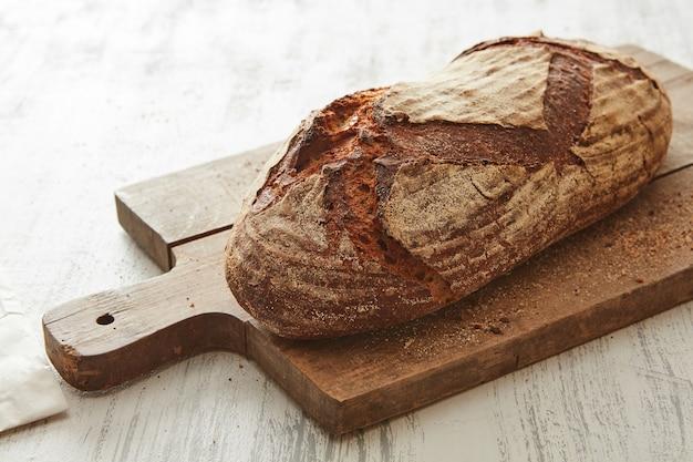Primo piano di pane fresco su una tavola di legno su sfondo chiaro