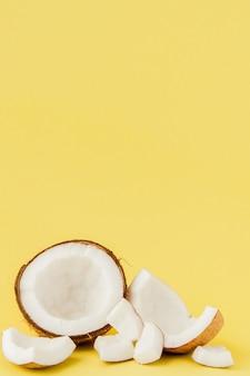 Close up cocco fresco pezzi isolati su uno sfondo giallo, frutta tropicale concetto, piatto laici, pop art, copia dello spazio.