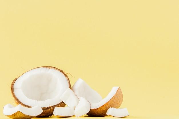 Close up cocco fresco pezzi isolati su uno sfondo giallo, concetto di frutta tropicale, piatto laici, pop art, copia dello spazio.