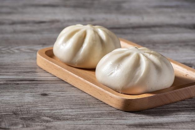 Primo piano di baozi delizioso fresco, panino di carne al vapore cinese è pronto da mangiare sul piatto di portata e sul piroscafo, close up, concetto di design del prodotto spazio copia.