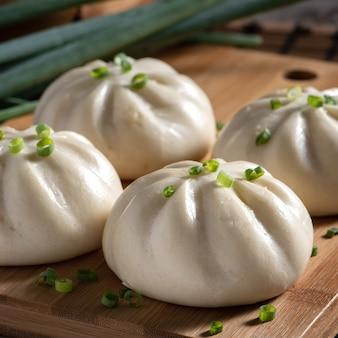 Primo piano di baozi delizioso fresco, panino di carne al vapore cinese è pronto da mangiare sul piatto di portata e vapore, close up, concetto di design del prodotto spazio copia.