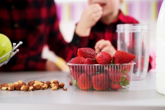 Chiuda in su delle fragole fresche e sane in ciotola di plastica e nocciole su un contatore in una cucina molto luminosa.