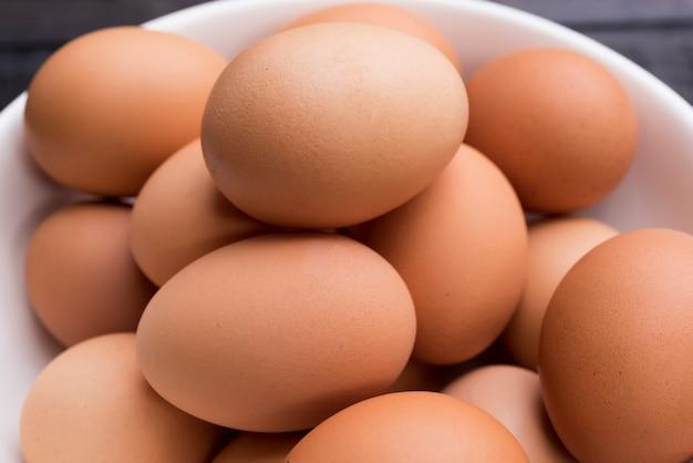 Chiuda in su gee gallina fresca nella ciotola bianca sulla tavola di legno