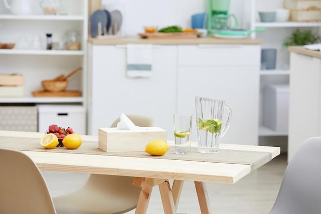Close-up di limonata fresca e frutta sono sul tavolo di legno nella moderna cucina della casa
