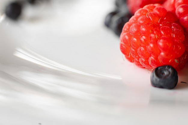 Chiuda in su della miscela di bacche fresche estive organiche nel piatto bianco. concetto di cibo sano. copia spazio