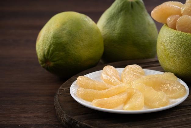 Primo piano di pomelo sbucciato fresco sul fondo della tavola di legno per la frutta del festival di metà autunno.