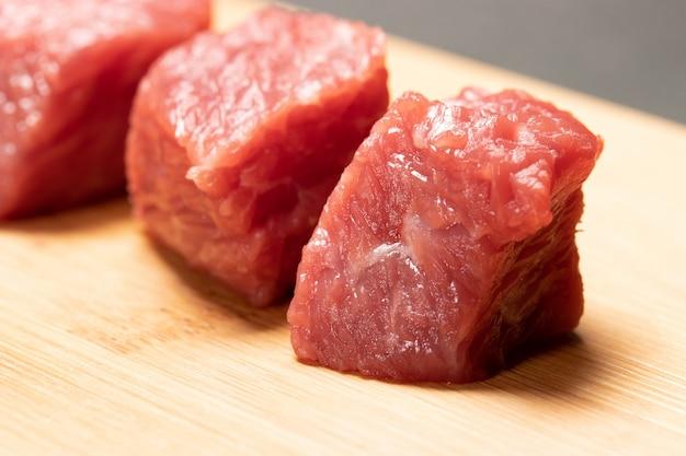 Primo piano della carne tagliata a cubetti cruda fresca sul tagliere