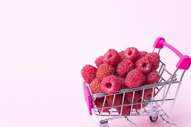 Chiuda sui lamponi maturi freschi nel carrello del supermercato, concetto sano di alimentazione, fondo dell'alimento