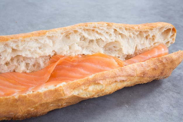 Chiuda in su del panino di color salmone fresco sulla tabella grigia e sulla stuoia di posto