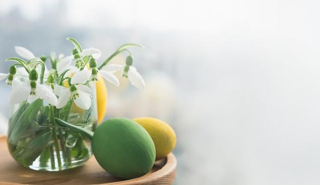 Close up bucaneve freschi in un vaso di vetro e uova di pasqua. banner con copia spazio