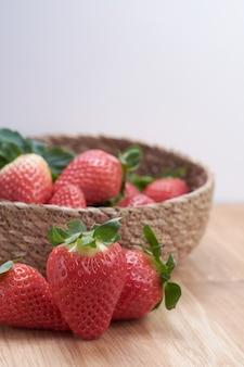 Chiuda sulle fragole fresche con fondo di legno naturale in un canestro