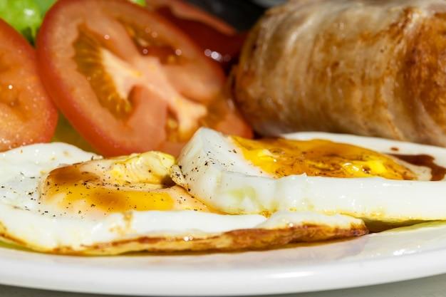 Close up uova fritte e salsicce e pomodoro sono stati posti su un piatto bianco per la colazione.