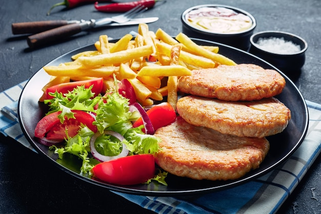 Primo piano di hamburger di tacchino fritti serviti con insalata di pomodori lattuga e patatine fritte su un piatto nero su un tavolo di cemento, con ketchup e senape, vista orizzontale dall'alto