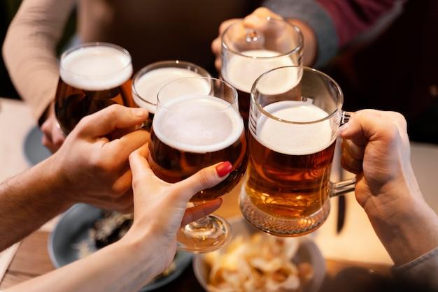 Amici del primo piano che tengono i boccali di birra