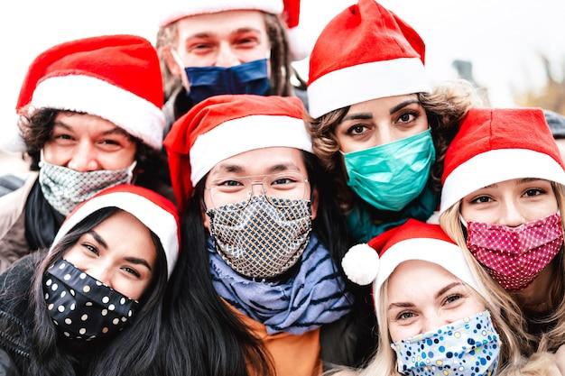 Close up di amici che prendono selfie di natale che indossa la maschera per il viso e santa hat