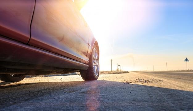 Chiuda sulla parte anteriore di nuova automobile rossa sulla strada asfaltata un giorno soleggiato