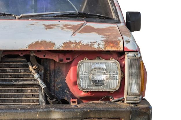 Chiuda sulla parte anteriore di vecchia automobile arrugginita isolata su priorità bassa bianca