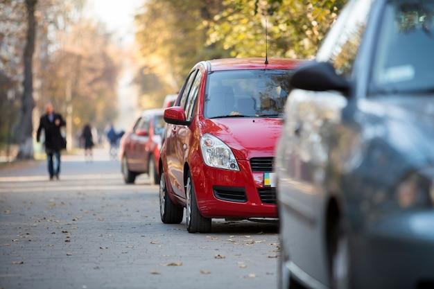 Dettaglio di vista frontale del primo piano della macchina lucida rossa brillante parcheggiata sul marciapiede