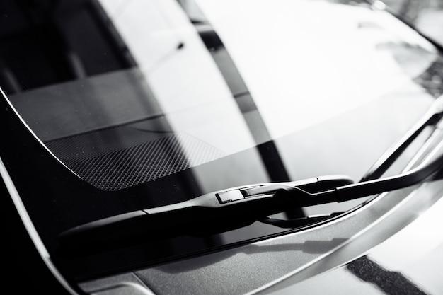 Chiuda in su dei tergicristalli anteriori su un'auto nuova nera in salone.