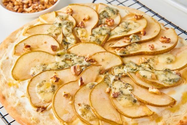 Close up di frutta fatta in casa dolce pera pizza con formaggio e miele, cibo salato italiano rustico con pasta frolla