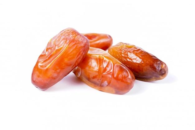 Chiuda sui frutti della palma da datteri su fondo bianco