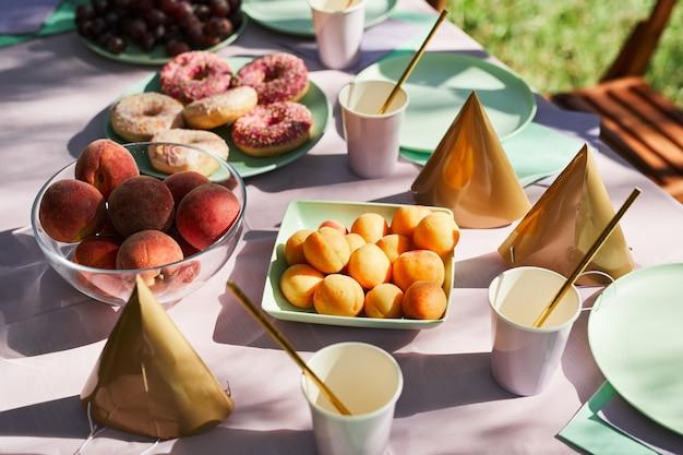Primo piano di frutta e dolci sul tavolo da picnic all'aperto decorato per la festa di compleanno in estate copia s...