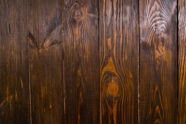 Primo piano completo di tavole di legno marrone scuro con grana e nodi visibili