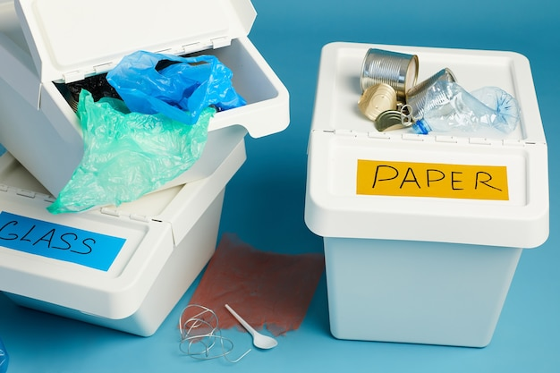 Primo piano di bidoni della spazzatura pieni per rifiuti di plastica e carta, cernita e concetto di riciclaggio