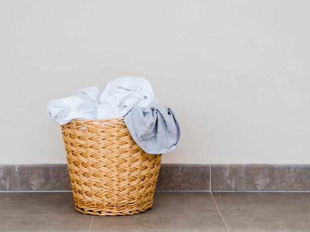 Chiuda sul cestino di lavanderia pieno del ramoscello