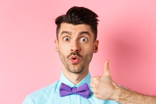 Primo piano del ragazzo divertente con i baffi, dire wow e mostrando il pollice in segno di approvazione, controllando qualcosa di interessante, raccomandando il prodotto, in piedi su sfondo rosa.