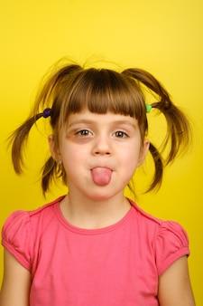 Primo piano della bambina divertente con l'occhio contuso che mostra la sua lingua